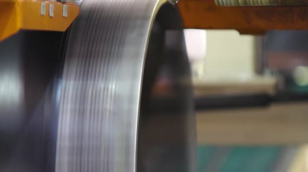 fedél : Rubber tape is reeled up on a drum in the machine. Production process of tires on modern equipment in the factory. Robotic machine in a tire factory. Mechanical engineering and heavy industry.