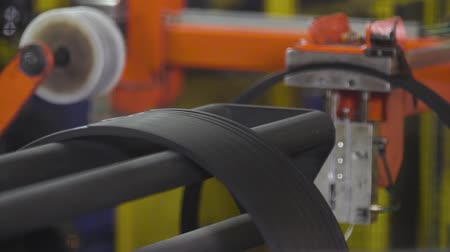reinforced : Reinforced with wire modern tires in a factory. Reinforced steel bronzed wire side rim on the tire. Automated production of side rims for car tires. Tyre production machine. Modern machine tools. Stock Footage