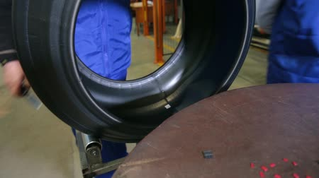mold : Worker prepares tire for the next production phase. Detailed production process of car tires, close-up. Car tires production. Manufacture of automobile tyres. Tyre production machine conveyor.