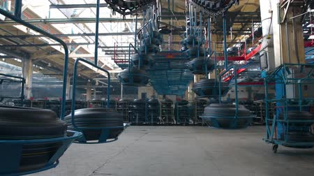 mold : Ceiling conveyor works on the forming workshop on tires plant. Tire blanks move on conveyor through shop. Conveyor with tyres at factory. Transport system in a tyre factory. Large car tire factory.