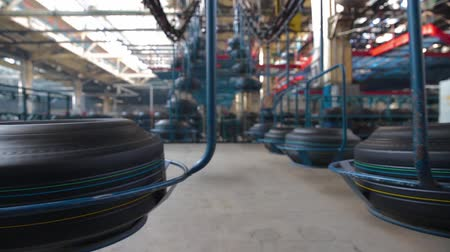 mold : Tire blanks move on the conveyor through the shop. Large car tire factory. Tire moves on the conveyor at factory. Air conveyor transfers tire from one operation to others above processing work shop.