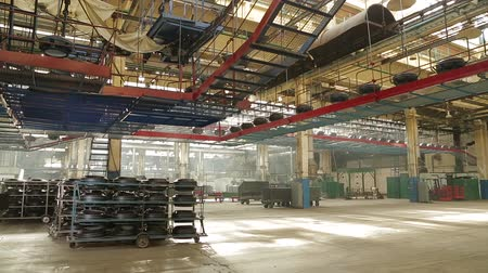 tag : Ceiling conveyor works on the forming workshop on tires plant. Tires production. Large car tire factory. Moving conveyor transfers formed rubber tires along large manufacturing plant workshop.