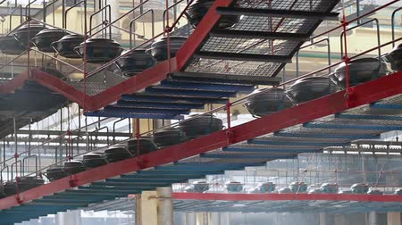 molde : Conveyor with tires at factory. Tires production. Large car tire factory. Air conveyor transfers tire from one operation to others above processing work shop. Manufacture of automobile tyres. Stock Footage