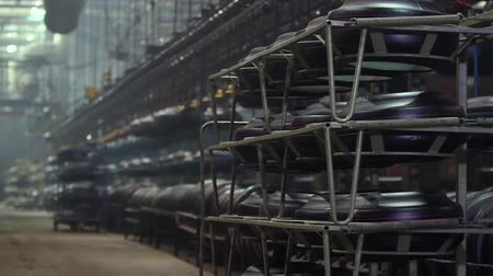 detalhado : Tire blanks are stacked in the workshop. Tires on conveyor in the tire pressing shop. Large car tire factory. Interior tire factory with overhead conveyors. Manufacture of tires. Large tire factory.
