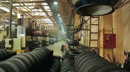 şekillendirme : Manufacture of tires. Tyre production machine conveyor. Process of forming tires in a factory. New cars tires stacking up at workshop. Tire blanks move on the conveyor through the shop.