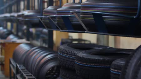 tread : Stacks of new tires in the shop near transport conveyor, which feeds tire blanks to the pressing machines. Large workshop with wheels at a tire factory. Group of new tires for sale at a tire store.