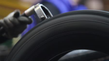 koruyucu : Tool for stripping tires after molding. Tire handling at the factory from excess rubber. Car tiyes production. Detailed production process of car tires, closeup. Rotation of the wheel close up.