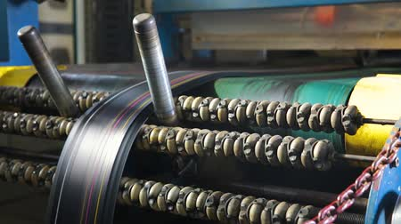 componentes : Manufacture of tires. Machine for marking rubber bands with colored paints cutting into pieces for the further production of automobile tires. Cutting rubber bands into pieces at a tire factory.