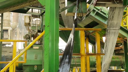 componentes : Rubber tape is fed into the machine for further forming and processing at a chemical plant. Rubber band before molding at a tire factory. Recycling and waste of the chemical industry. Refinery waste.