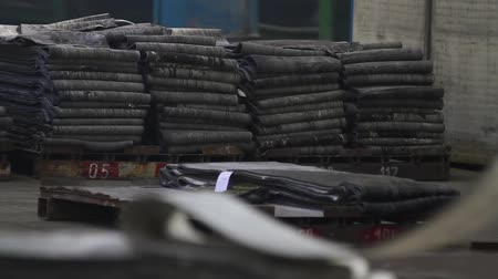 нефтехимический : Large piles of rubber tape in the tires factory. Recycling rubber in the chemical industry. Industrial space at tire factory. Tyre production machine. Rubber tape on a large tire factory close up.