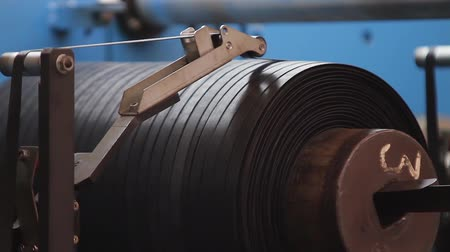 нефтехимический : Narrow black rubber band between the machine rollers is wound onto a spool. Rubber tape on a large tire factory close up. Rubber tape is reeled up on a drum in the machine. Car tires production.