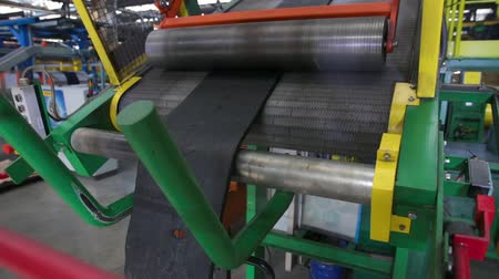 componentes : Rubber tape is fed into the machine for further forming and processing at a chemical plant. The initial stage of production of automobile tires. Rubber tape is reeled up on a drum in the machine.