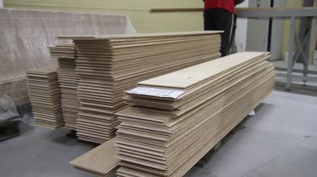 паркет : Piles of laminated floor panels in the workshop interior. Laminated floor production line. Factory for the production of laminate floor panel. Laminated flooring.