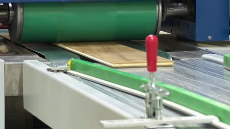 preslenmiş : Machine for gluing laminated floor panels. Gluing laminate to a wooden base under pressure and heat. Stok Video