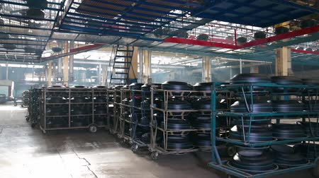 tag : Interior tire factory with overhead conveyors. Manufacture of tires. Tyre production machine conveyor. Tire blanks move on the conveyor through the shop. Large car tire factory. Stock mozgókép