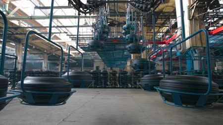 tag : Moving conveyor transfers formed rubber tires along large manufacturing plant workshop. Interior tire factory with overhead conveyors. Conveyor with tires at the factory. Large car tire factory.