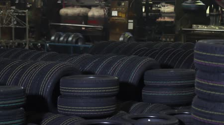 プロテクター : New tires stacked and sorted. Tires on conveyor in tyre pressing shop. New tyres in industrial workshop. New qualitative black rubber tire with colored marks on deep protector transported by conveyor.