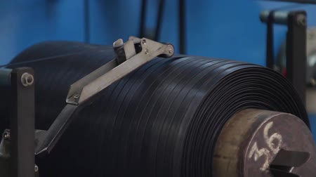 нефтехимический : Rubber tape is reeled up on a drum in the machine. Narrow black rubber band between the machine rollers is wound onto a spool. Rubber production line rubber chemical production. Tires production.