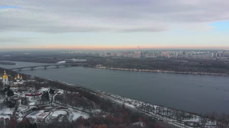 Kiev city is the capital of Ukraine in winter. Flight over Kiev in winter with a view of the Dnieper River in the evening. Panorama of Evening Kiev with dramatic clouds. Stock Footage