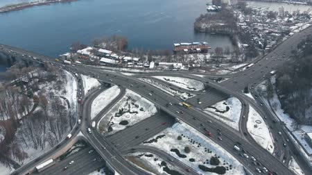 Road junction with heavy traffic in Kyiv, Ukraine. View from above, winter time. Aerial view footage of traffic two-level junction, slow moving cars by intersection of roads, bridges. Urban Kyiv city.