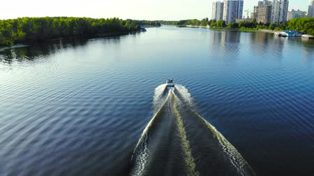 Speed boat moving fast on the river. Aerial view of a white motor boat sailing on a blue river in the city. Boat fast sailing on the river, rear view. Stock Footage