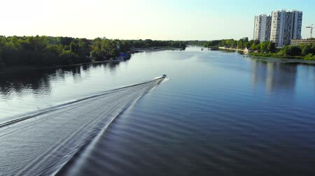 Boat sailing on a wide river, rear view from above. Small white motor boat swims quickly along the river, moving into the distance. Stock Footage
