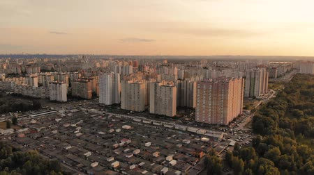 Outskirts of a large city with tall apartment buildings. Panorama of the city from a high angle from left to right. Warm toning, summer evening city. Drone flies over the evening city in sunset light.