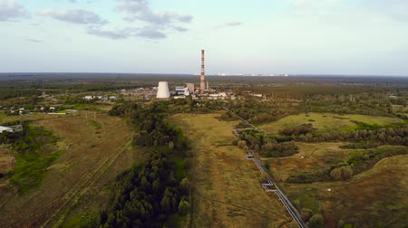 Aerial drone view of pipes and cooling towers of coal thermal power plant. Pipes of a heating main stretch into the city. Thermal power plant does not work in the summer.