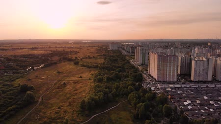 Aerial view of a large number of big houses on the outskirts of the city on an summer at sunset with the road and cars. Air pollution over a big city, concept.