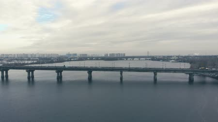 Traffic on a bridge over a wide river in the winter. Drone is approaching the automobile bridge, view from above. Cars move on the bridge in both directions. Cold tinting in the winter.