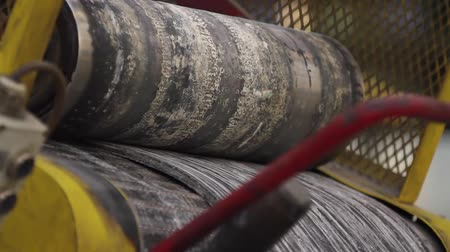 нефтехимический : Rubber band before molding at a tire factory. Recycling and preparation of rubber mixture for production of automobile tires. Rubber tape is reeled up on a drum in machine. Tires production factory.