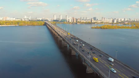 Flying over the bridge on which cars move. In the background is a large city with skyscrapers and modern buildings on a sunny bright day. A long bridge over a wide river. Aerial view. Autumn time.