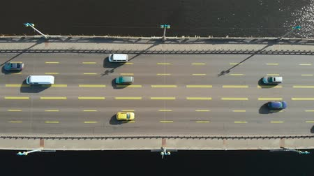 мостовая : Bridge, view from the top. Camera takes off right above the bridge on which cars go in both directions. Road bridge with a wide road for cars. Bridge over the water, flat lay. Zoom out, aerial view.