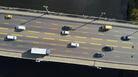 axe : Bridge with driving cars, view from the top. Camera rotates around an axis and goes down above the automobile bridge on which cars are driving. Aerial view of car traffic on the Paton bridge, Kiev