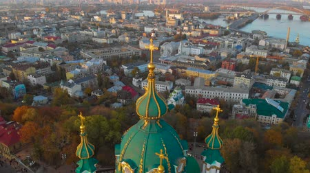 fly away : Panorama of the city of Kiev with the domes of St. Andrew at sunset. Flying above and around St. Andrews Church in Kiev at sunset. The drone camera moves back and flies over the domes of St. Andrew. Stock Footage