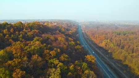 külvárosok : Aerial view of road in beautiful autumn forest at sunset. Beautiful landscape with empty rural road, trees with orange leaves. Highway leading to city from autumn forest. Top view from flying drone.
