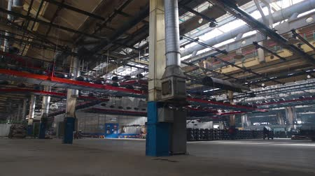 tag : Tire moves on the conveyor at factory. Interior tire factory with overhead conveyors. Large car tire factory. Moving conveyor transfers formed rubber tires along large manufacturing plant workshop.