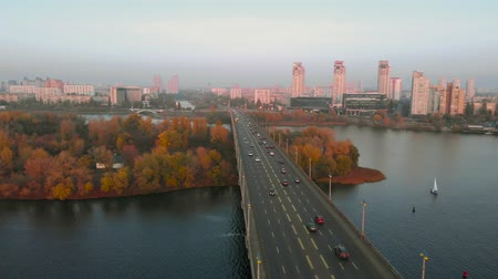 Bridge over a wide river with cars traveling top view. The camera flies over the automobile bridge, cars move to the corridor in obesity, at sunset. Autumn city landscape.