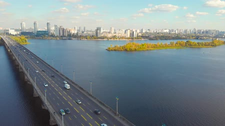 Flying back over the bridge across the wide Dnieper River, Kiev, Ukraine. Cars move on a road bridge over a river. Modern city and autumn yellow trees on a background. Autumn time.