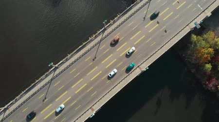 Aerial view, top down view of traffic on a car bridge. Bridge over the water near shore, top view. Aerial top view of bridge road over river with car traffic, city transportation concept, 4K video Stock Footage