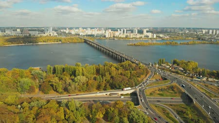 View of the city of Kiev across the Dnieper River, with a long bridge in the foreground. The bridge over the Dnieper River. In the background is Kiev with modern buildings and skyscrapers. Aerial view