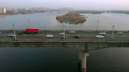 мостовая : Red truck without identifiable signs rides on a road bridge over a river. The camera tracks a red truck driving over a bridge at sunset time.