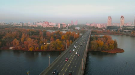 Drone flying over an automobile bridge in fall at sunset. In background is a modern metropolis in rays of setting sun. Cars drive from one shore to another. An island with autumn trees in a cityscape.