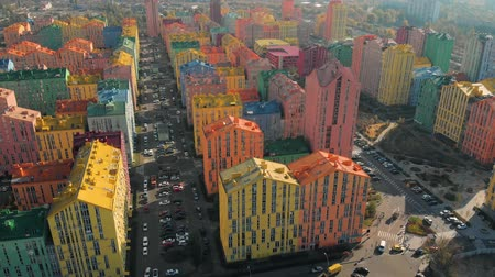 Colored residential buildings. Multicolor houses in the city. Drone fall down near a modern residential complex with colorful houses similar to a constructor on a bright sunny day. Aerial view. Stock Footage
