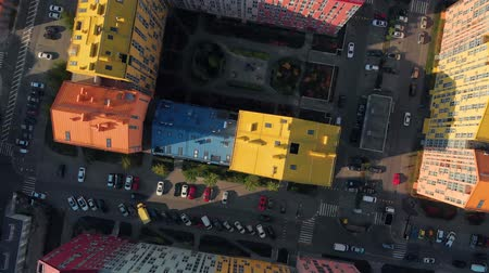 Top down view of infrastructure of a modern residential area with colorful houses. City streets with parked cars between colorful houses. Top down view, drone video footage. City life, top down view.