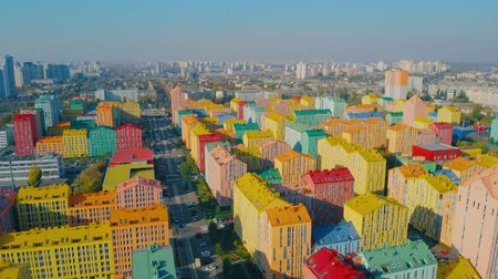 Residential quarter with multicolored houses similar to a constructor on a bright sunny day. Panoramic aerial view of colorful (red, green, blue, yellow) buildings on city street. Horizontal panorama. Stock Footage
