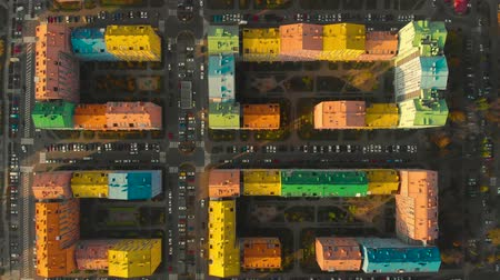 Top down view on the roofs of colorful houses of a residential area in city at sunset. Top view of the colorful buildings, aerial footage from the drone on Comfort Town. Residential district in Kiev. Stock Footage