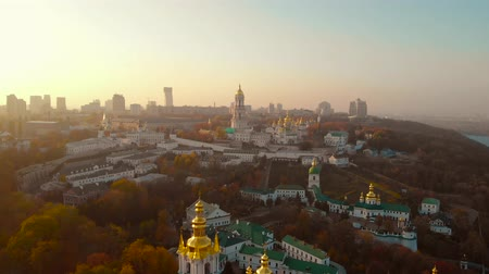 Golden foggy sunset evening in Kiev Ukraine. Kiev Pechersk Lavra. Architecture Kiev Pechersky Monastery on sunset sky and modern Kiev City background. Aerial drone video footage. Stock Footage