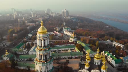Kiev Pechersky Monastery on sunset fog sky and modern Kiev City background. Archutecture Kiev Pechersk Lavra on evening city landscape. Camera moves forward. Aerial view, drone video footage. Stock Footage