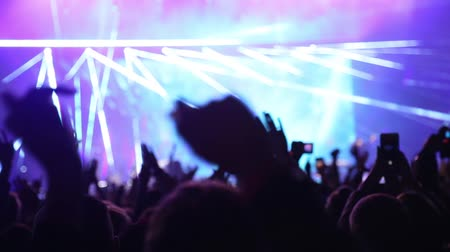 People cheer move lift and clap their hands in unison against the strobing stage lights. Young people lifestyle and nightlife. Laser show on live music concert. Handheld live video footage. 무비클립